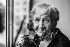 Porträt einer älteren Frau auf dem Dachboden mit Blumen Stockfotografie