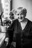 Porträt einer älteren Frau auf dem Dachboden mit Blumen Lizenzfreie Stockfotos