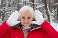 Porträt einer älteren Frau des Spaßes im Winterschneeholz im roten Mantel Stockbild