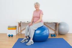 Porträt einer älteren Frau, die auf Eignungsball sitzt stockfotos