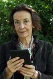 Porträt einer älteren Frau, die ein eBook liest Stockbilder