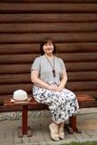 Porträt einer älteren Frau in einem grauen Leinenkleid, das auf einer Holzbank nahe einem Blockhaus im Dorf sitzt stockbilder