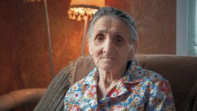Porträt einer älteren Frau 80-90 Jahre alt zu Hause Alte sonderbare Dame mit dem geknitterten Hautgesicht, das Kamera betrachtet  stock video footage