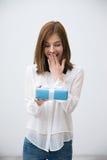 Porträt einer überraschten attraktiven Frau, die Geschenk hält Stockbilder