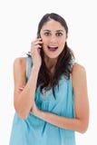 Porträt einer überraschten Frau, die einen Telefonanruf macht Stockbild