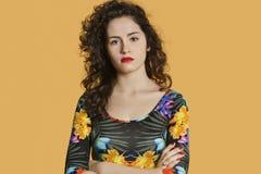 Porträt einer überzeugten jungen Frau mit den Armen kreuzte über farbigem Hintergrund Stockbild