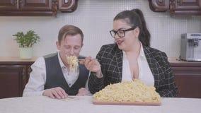 Porträt einer überzeugten prallen Frau in der Küche am Tisch vor einer großen Platte mit Nudeln Das Mädchen, das zu versucht stock video