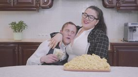 Porträt einer überzeugten prallen Frau in der Küche am Tisch vor einer großen Platte mit Nudeln Das Mädchenumarmen stock video