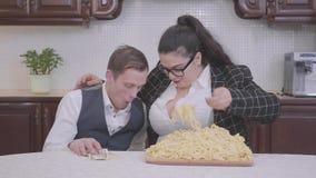 Porträt einer überzeugten prallen Frau in der Küche am Tisch vor Platte mit Nudeln Das Mädchen, das versucht einzuziehen stock video