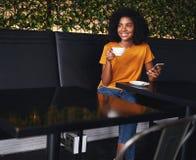 Porträt einer afrikanischen jungen Frau, die im Café sitzt stockbilder