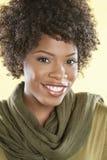 Porträt einer Afroamerikanerfrau, die mit einer Stola rund ihr Hals über farbigem Hintergrund lächelt Stockfotografie