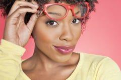 Porträt einer Afroamerikanerfrau, die Retro- Gläser über farbigem Hintergrund hält Lizenzfreie Stockfotografie