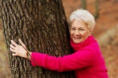 Porträt einer alten cherrful Dame, die nahe bei einem Baum steht. lizenzfreie stockfotografie