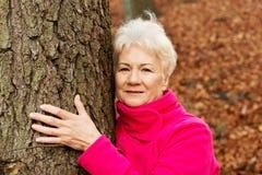 Porträt einer alten cherrful Dame, die nahe bei einem Baum steht. stockfotos