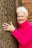 Porträt einer alten cherrful Dame, die nahe bei einem Baum steht. stockbild