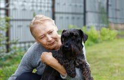 Porträt einer alten Frau, die schwarzen Hund hält lizenzfreie stockbilder