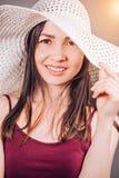 Porträt einer attraktiven Brunettefrau in einem beige Hut in der Sonne Junges Mädchen lizenzfreie stockbilder