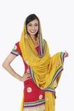 Porträt einer attraktiven indischen Frau in der traditionellen Abnutzung, die über weißem Hintergrund steht stockfotos