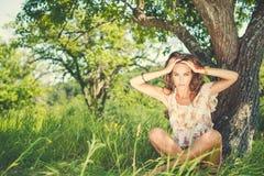 Porträt einer besorgten Frau, die unter Baum sitzt Stockfotografie