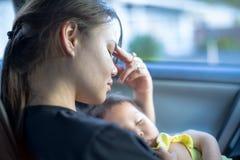 Porträt einer betonten Mutter, die versucht fertig zu werden, während sie ihr schlafendes Baby in ihren Armen trägt stockfotografie