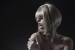 Porträt einer blonden Frau über einem dunklen Hintergrund stockbild