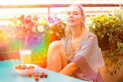 Porträt einer blonden Frau, die auf Balkon sitzt lizenzfreie stockfotografie
