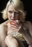 Blonde Frau, die einen rosa Martini trinkt Stockfotografie