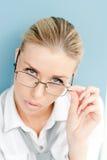 Porträt einer blonden jungen Geschäftsfrau, die über quadratischen Schauspielen schaut Stockfotografie