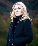 Porträt einer Blondine im Mantel Stockfotos