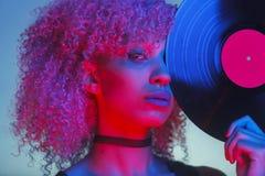 Porträt einer Discofrau, die ein Vinyl mit Musik der Achtziger Jahre hält Lizenzfreie Stockfotografie