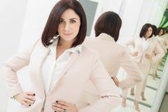 Porträt einer dunkelhaarigen attraktiven Frau, die in der beige Klage gekleidet wird Stellung im vorderen Spiegel stockbild