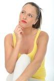 Porträt einer durchdachten jungen Frau, die ein Problem erwägt Stockfotografie