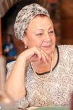 Porträt einer eleganten älteren Dame, die am Feiertagstisch sitzt stockfoto