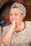 Porträt einer eleganten älteren Dame, die am Feiertagstisch sitzt lizenzfreies stockbild