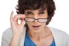 Porträt einer entsetzten Frau, die über ihren Gläsern schaut Stockbild