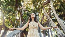 Porträt einer entspannten Frau, die über dem Regenwald aufwirft stockfoto