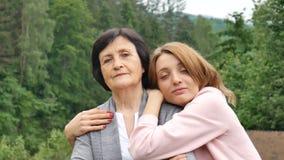 Porträt einer ernsten Mutter und der erwachsenen Tochter gegen den Hintergrund der Berge im Sommer Gl?ckliches hohes Alter stock footage