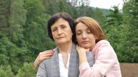 Porträt einer ernsten Mutter und der erwachsenen Tochter gegen den Hintergrund der Berge im Sommer Gl?ckliches hohes Alter stock video