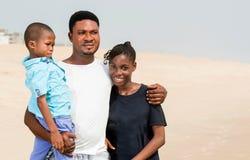Porträt einer Familienstellung am Strand lizenzfreies stockbild