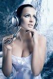 Porträt einer Frau in den Kopfhörern auf einem Winterhintergrund Stockfotografie