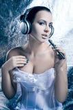 Porträt einer Frau in den Kopfhörern auf einem Winterhintergrund Stockfotos