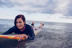 Porträt einer Frau, die über Surfbrett im Wasser schwimmt Lizenzfreie Stockfotos