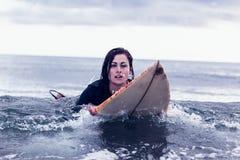 Porträt einer Frau, die über Surfbrett im Wasser schwimmt Lizenzfreies Stockfoto