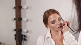Porträt einer Frau, die auf die Fertigstellung des Makes-up im Studio wartet stock video
