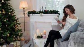 Porträt einer Frau, die ein Buch ein Mädchen liest einen Roman, die Kamera betrachtend liest, die lächelt, tragendes der jungen F stock video