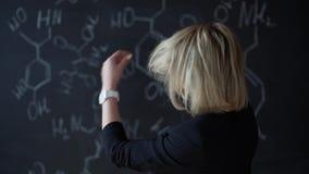 Porträt einer Frau, die eine schwierige Aufgabe, stehend nahe dem Brett mit Formeln löst Das Konzept der Wissenschaft plan stock video