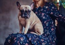 Porträt einer Frau, die mit einem netten Pug in einem Raum mit Dachboden sitzt Lizenzfreie Stockfotografie