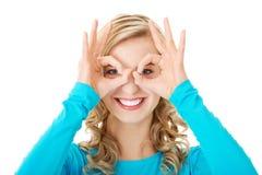 Porträt einer Frau, die okayzeichen auf Augen zeigt Lizenzfreie Stockfotografie