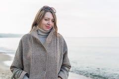 Porträt einer Frau in einem Mantel nahe dem Meer stockfotografie
