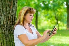Porträt einer Frau 50 Jahre alt mit einer Tablette Stockfotografie
